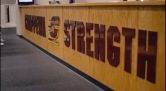 "The words ""Chippewa Strength"" are displayed on the desk in front of the chocolate milk machines in the Indoor Athletic Complex."