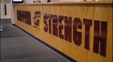 """The words """"Chippewa Strength"""" are displayed on the desk in front of the chocolate milk machines in the Indoor Athletic Complex."""