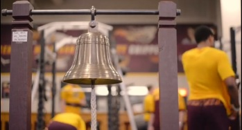 The bell sits behind the weight in the Indoor Athletic Complex for the athletes to ring when they get a lifting personal record.
